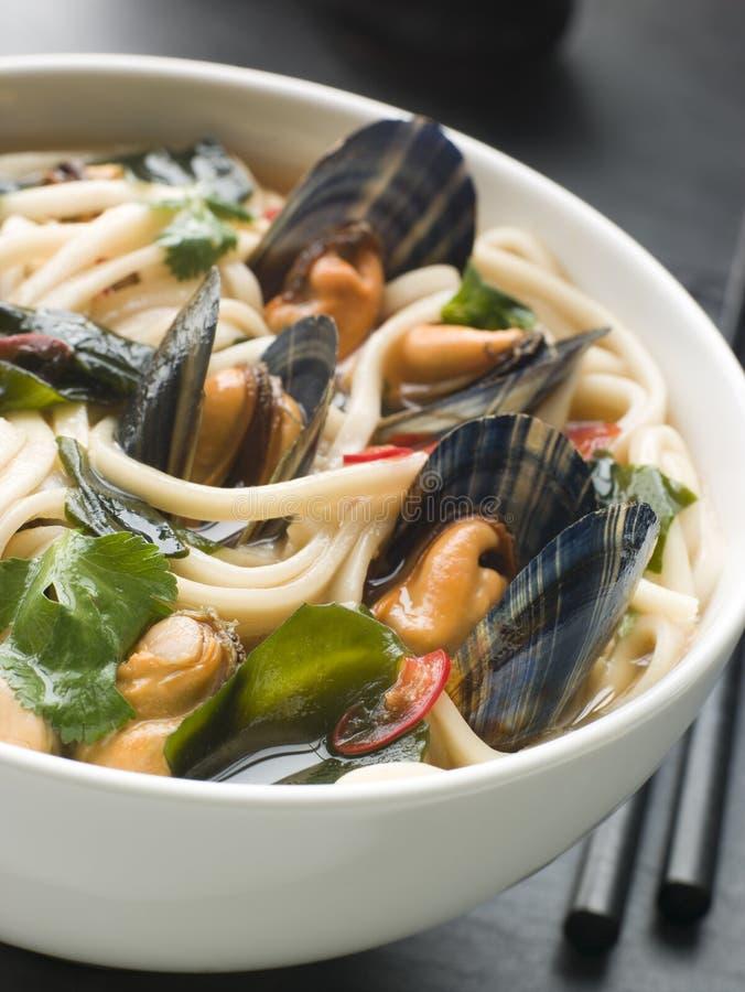 Mexilhões e macarronetes de Udon no caldo de carne da soja do pimentão imagem de stock
