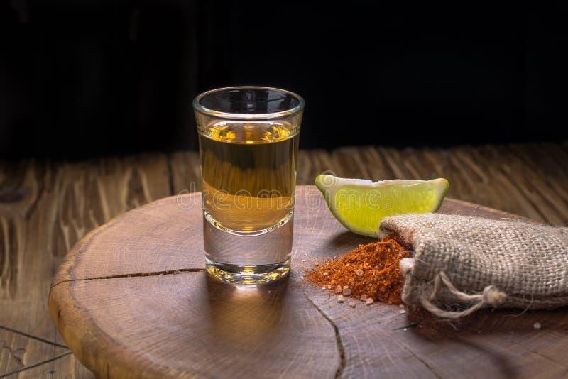 Mezcal - bebida alcohólica fuerte mexicana tradicional con las rebanadas de la cal y sal del gusano en un viejo tablero de madera imagenes de archivo
