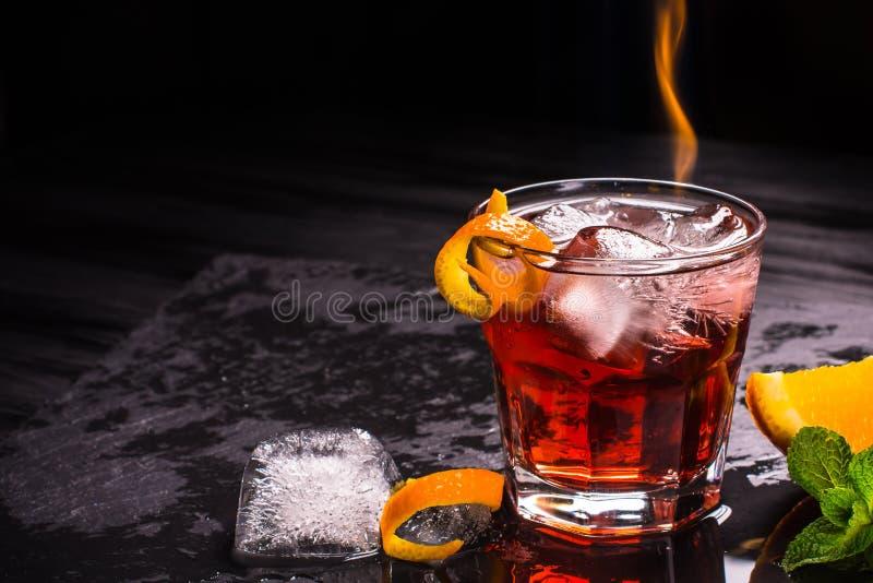 Mezcal Negroni coctail med flammor Rökig italiensk aperitivo Apelsin - makro fotografering för bildbyråer