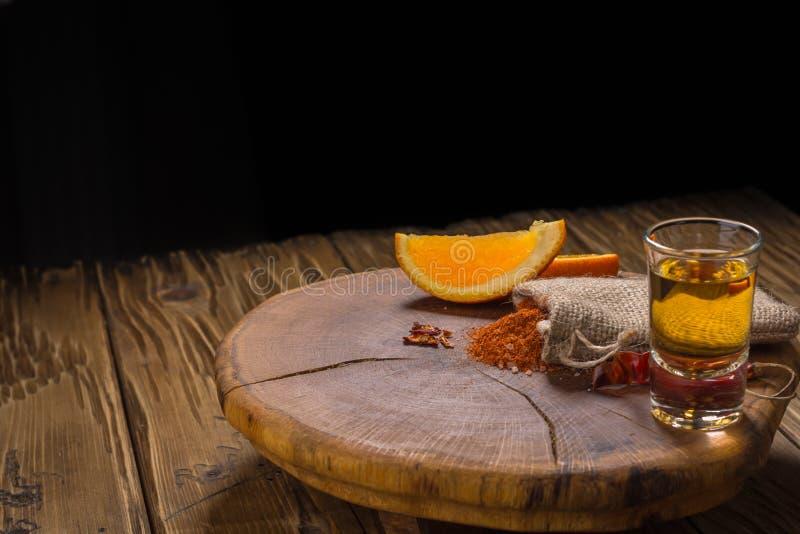 Mezcal schoot Mexicaanse drank met oranje plakken, Spaanse peperpeper en wormzout in oaxaca Mexico stock foto's