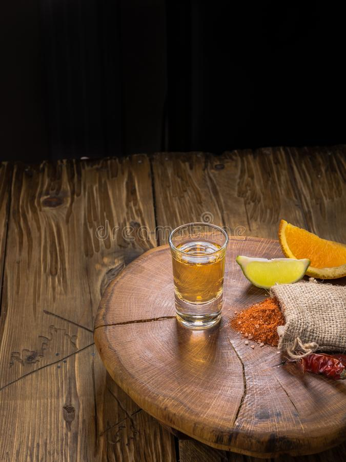 Mezcal shot mexican drink with orange and lime slices, chili pepper and worm salt in oaxaca mexico. Vertical. Mezcal mexican drink with orange, lime slices and stock photos