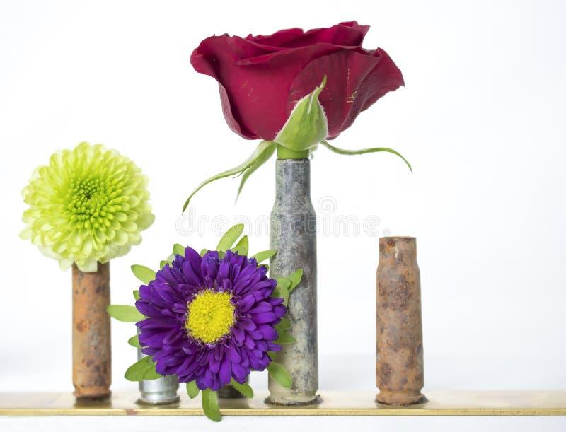 Mezcla brillante de flores en Bud Vases Made de las cubiertas de la bala fotografía de archivo