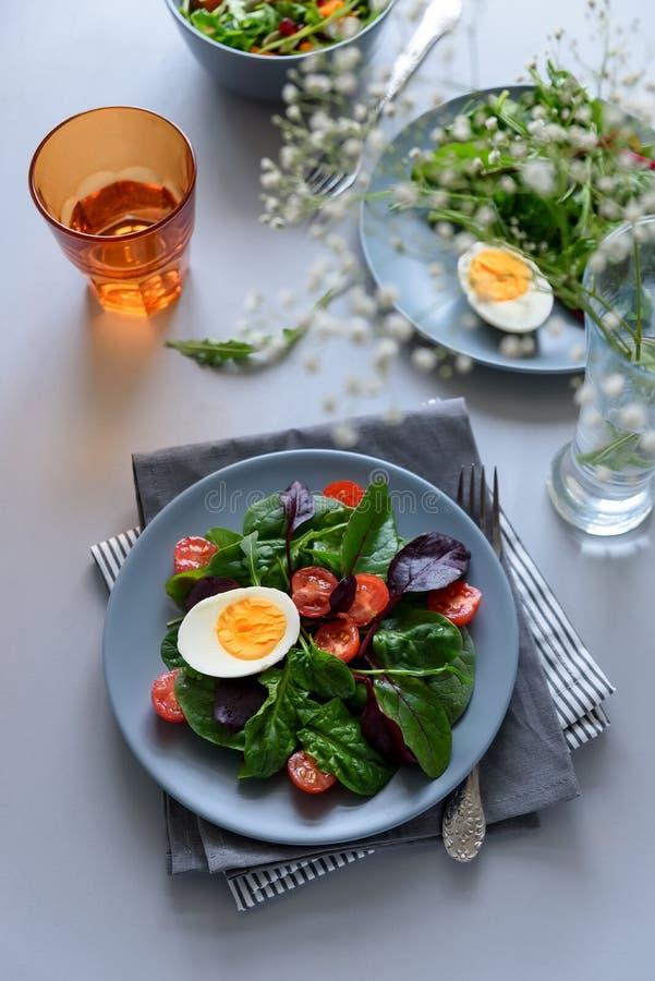 Mezcla de la ensalada con espinaca, arugula, hojas de la remolacha, tomates y huevos en fondo de madera gris Concepto vegetariano imagenes de archivo