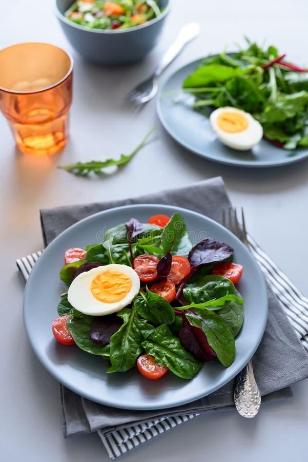 Mezcla de la ensalada con espinaca, arugula, hojas de la remolacha, tomates y huevos en fondo de madera gris Concepto vegetariano foto de archivo