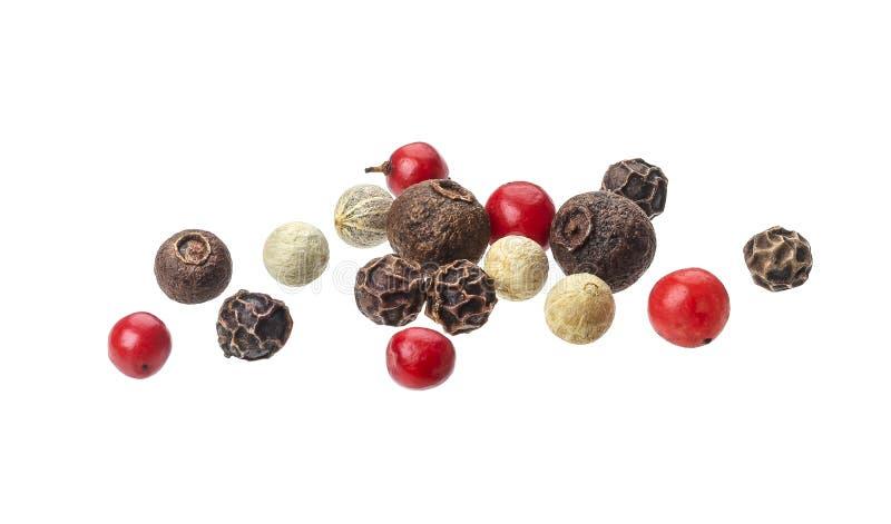 Mezcla de la pimienta Granos de pimienta negros, rojos, blancos y de la pimienta inglesa aislados en el fondo blanco, cierre para imagenes de archivo