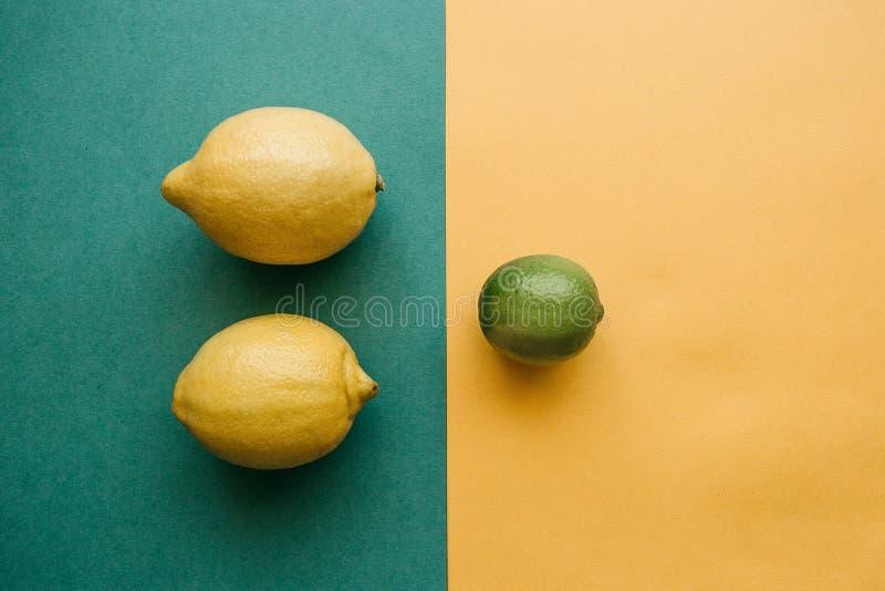 Mezcla de limones y de cal en un fondo coloreado imagen de archivo libre de regalías
