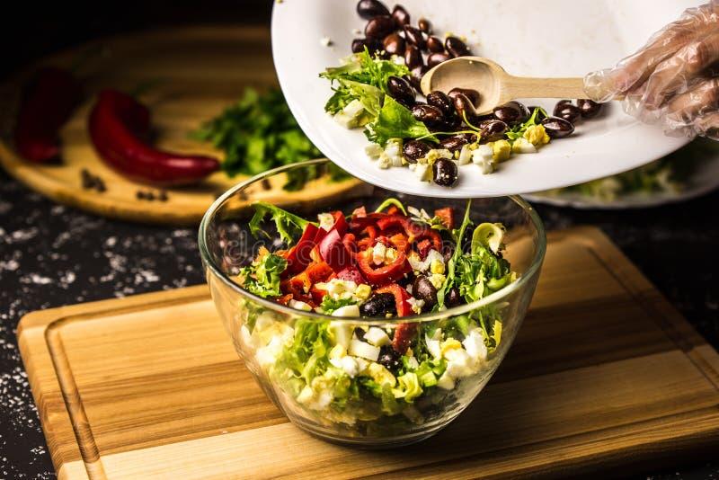 Mezcla de los ingredientes de la ensalada de la alubia negra, de la lechuga, de huevos y de la pimienta dulce en un bol de vidrio fotos de archivo libres de regalías