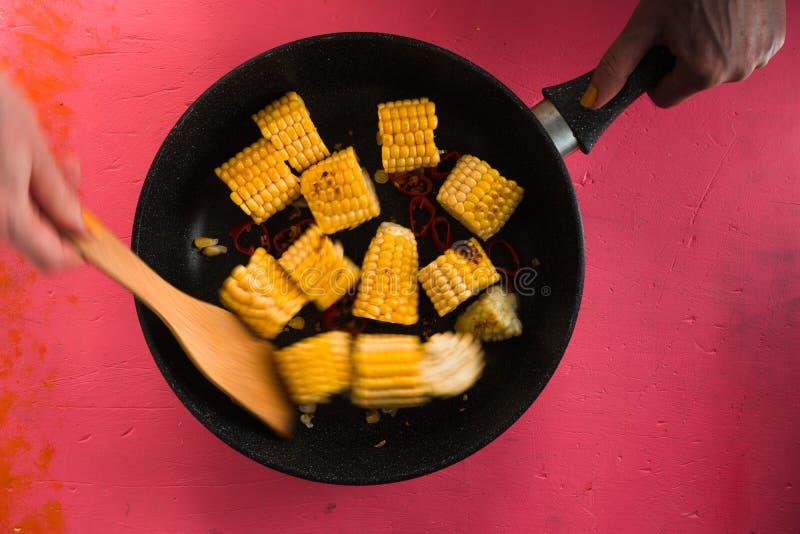 Mezcla de los pedazos de maíz en un sartén del arrabio fotografía de archivo