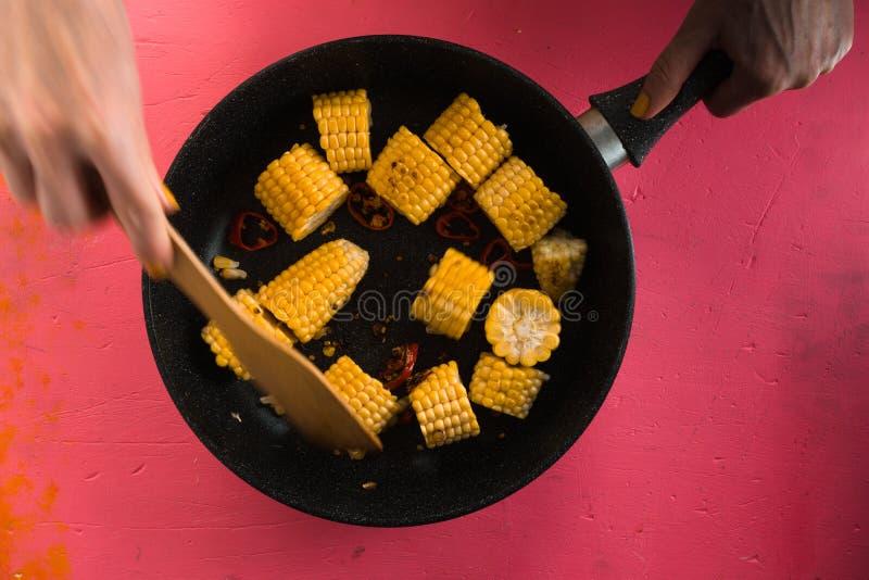 Mezcla de los pedazos de maíz en un sartén del arrabio en una tabla rosada fotografía de archivo