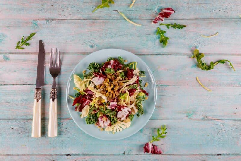 Mezcla fresca de ensaladas de kale, arugula, coliflor, brotes de bruselas y pistachos imagenes de archivo