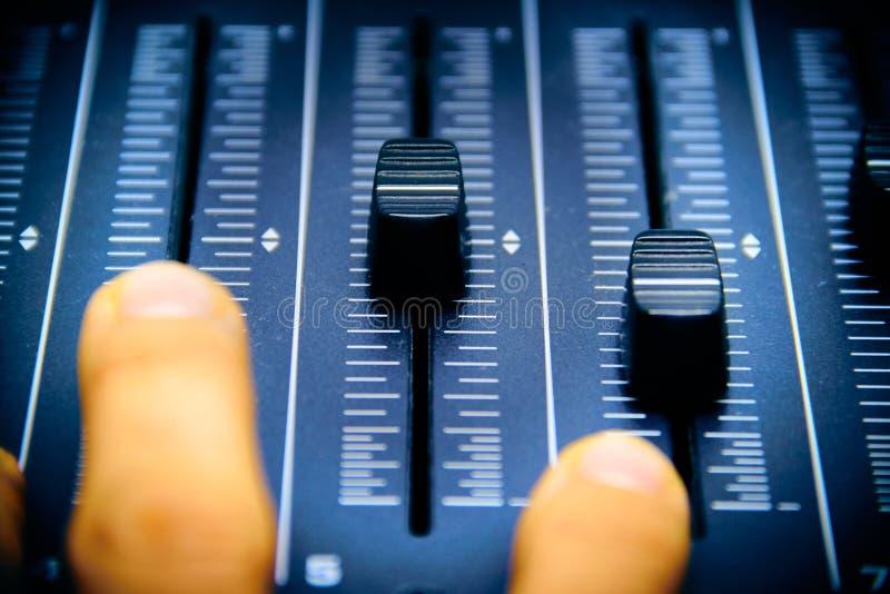 Mezclador audio, controles de mezcla y atenuador, consola de mezcla del escritorio de la m?sica con la mano del t?cnico que mueve imágenes de archivo libres de regalías