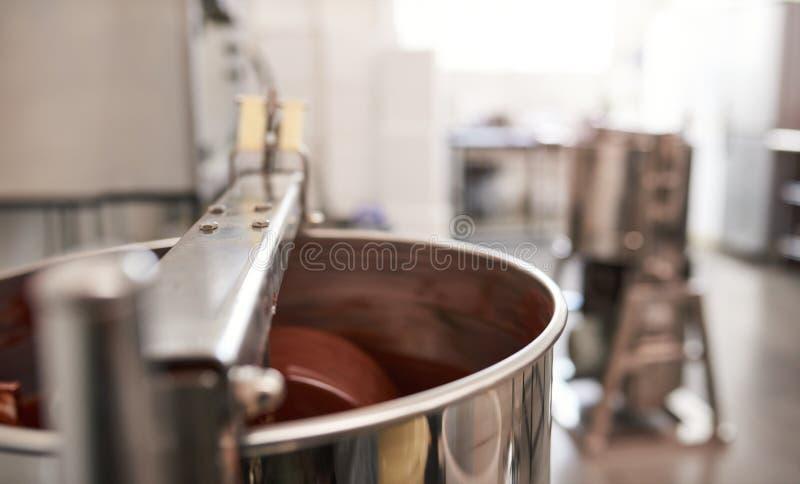 Mezclador de acero inoxidable que revuelve el chocolate derretido en un taller artesanal imagenes de archivo