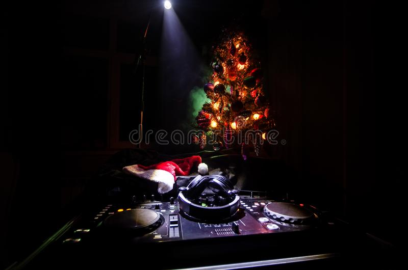 Mezclador de DJ con los auriculares en fondo oscuro del club nocturno con Noche Vieja el árbol de navidad Ciérrese encima de vist foto de archivo libre de regalías