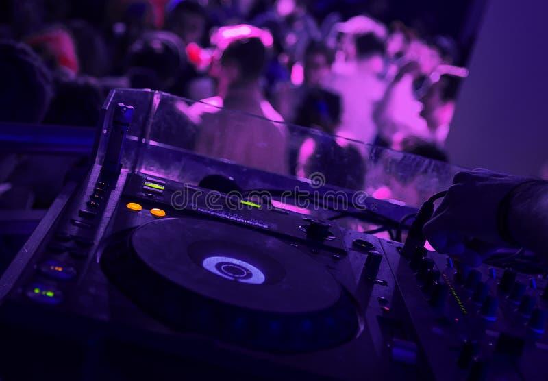 Mezclador en el club de noche con la gente en brackground imagenes de archivo