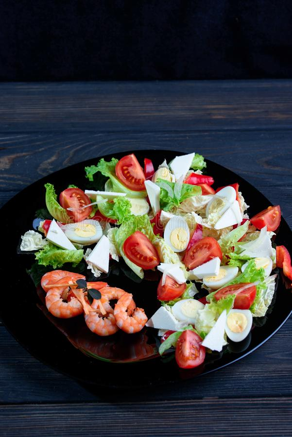 Mezcle la ensalada con las verduras frescas y los camarones del apetite en un p negro imagen de archivo