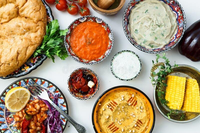 Meze traditionnel méditerranéen : houmous, babaganoush, harissa, tzatziki sur le fond blanc image libre de droits