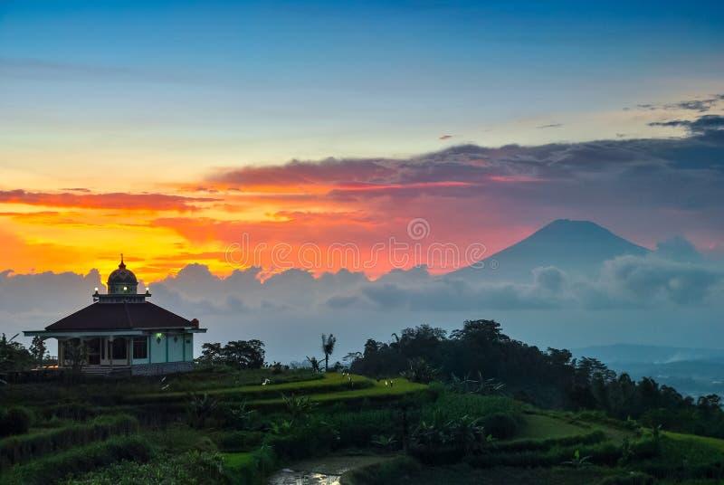 Mezquita y la puesta del sol con el fondo de la montaña imagen de archivo