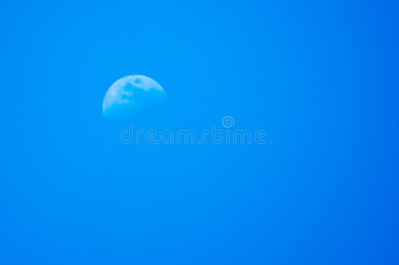 Mezza luna in cielo notturno blu fotografie stock
