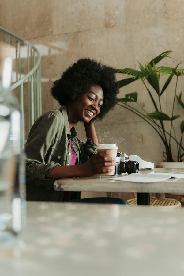 Mezza lunghezza di giovane donna africana felice che ha resto in self-service fotografie stock libere da diritti