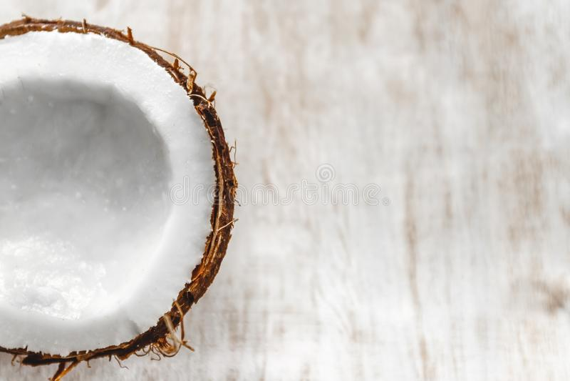 Mezza noce di cocco su un fondo di legno bianco leggero, primo piano Vista superiore immagini stock libere da diritti