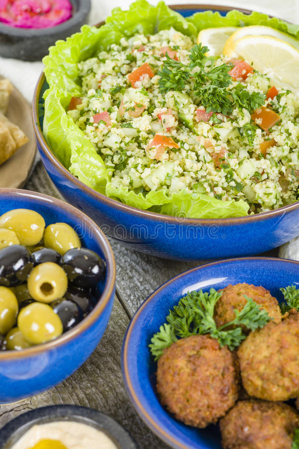 Mezze. Selection of Middle Eastern dishes. Tabbouleh, falafel, olives, sarma, spinach borek, fatayer, hummus and pita bread stock photo