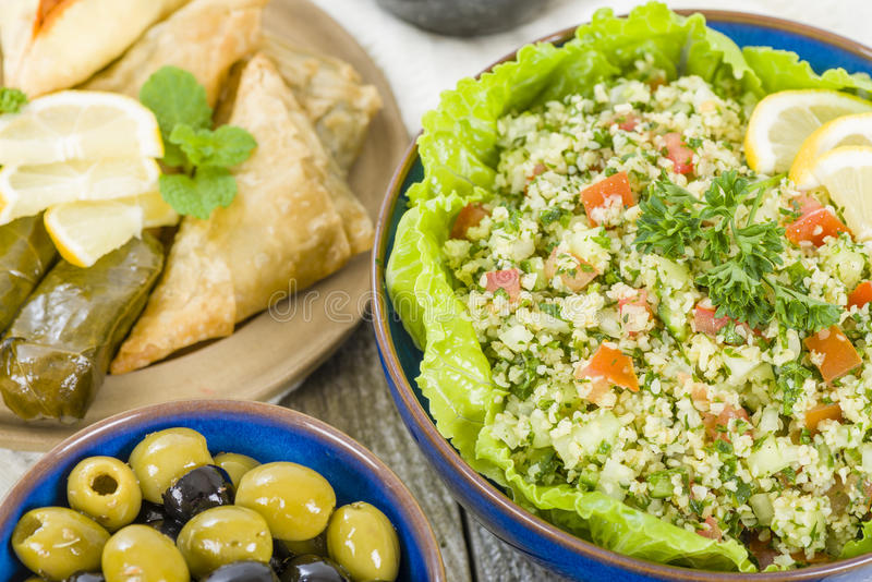 Mezze. Selection of Middle Eastern dishes. Tabbouleh, falafel, olives, sarma, spinach borek, fatayer, hummus and pita bread royalty free stock photos
