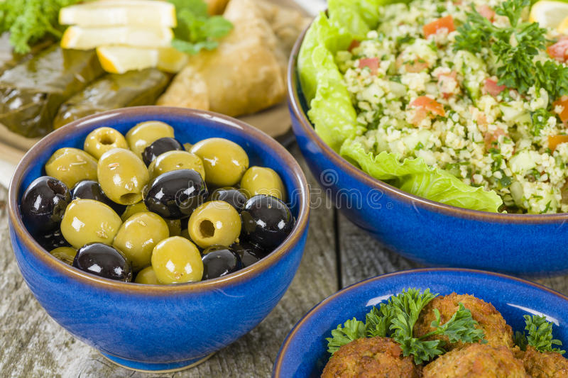 Mezze. Selection of Middle Eastern dishes. Tabbouleh, falafel, olives, sarma, spinach borek, fatayer, hummus and pita bread royalty free stock images