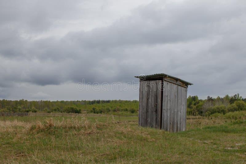 In mezzo al prato sta una toilette pubblica rustica fatta delle plance di legno fotografia stock libera da diritti