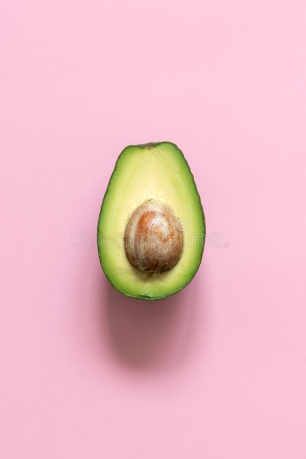 Mezzo avocado sul fondo di rosa pastello minimalism immagini stock libere da diritti