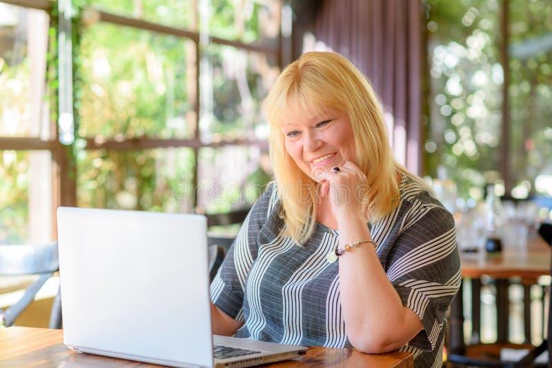 Mezzo elegante del ritratto invecchiato più la donna di affari di dimensione che lavora al computer portatile in ufficio o caffè  immagini stock