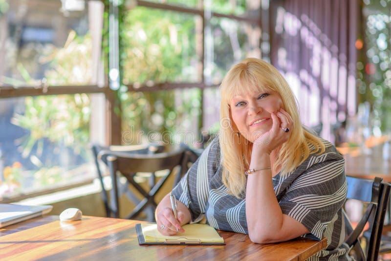 Mezzo elegante del ritratto invecchiato più seduta della donna di dimensione e che fa le note al suo diario sul balcone o sul ter fotografia stock