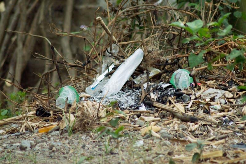 Mezzo ha carbonizzato i mucchi di spreco di plastica nell'ambiente circostante immagini stock libere da diritti