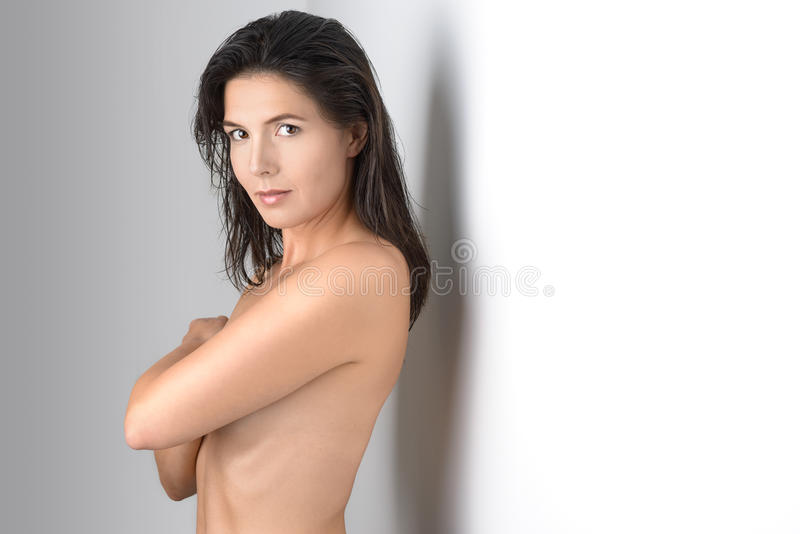 Mezzo invecchiato ghignando donna che copre il suo petto immagini stock libere da diritti