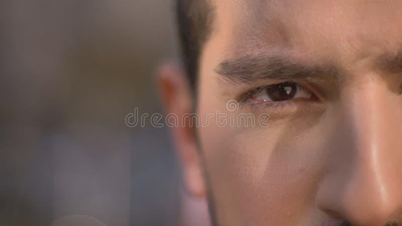 Mezzo ritratto del primo piano dell'uomo caucasico che guarda seriamente nella macchina fotografica sul fondo della via fotografia stock