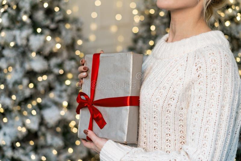 Mezzo ritratto di lunghezza di bella ragazza bionda che posa con il regalo in mani fotografia stock