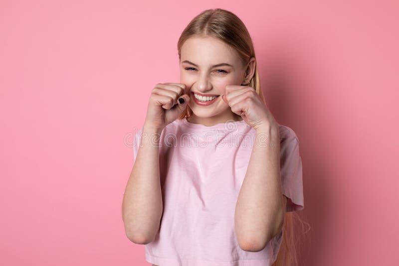 Mezzo ritratto di lunghezza di bella ragazza bionda con gli occhi azzurri, maglietta rosa d'uso, con i pugni vicino al fronte immagine stock libera da diritti