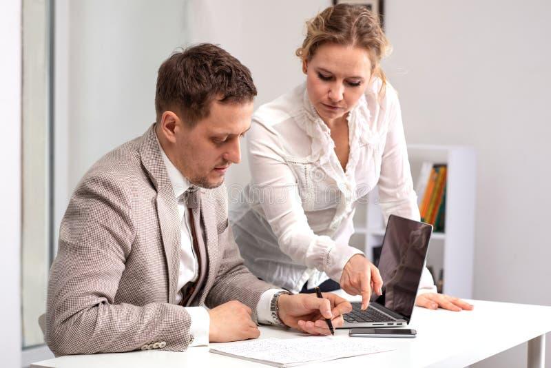 Mezzo ritratto di lunghezza del giovane che indossa seduta beige del vestito che lavora al suo computer portatile Una donna, un c fotografia stock libera da diritti