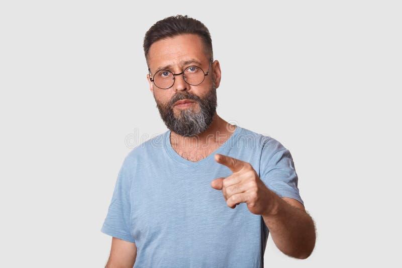Mezzo ritratto di lunghezza dell'uomo invecchiato medio attraente con scoperto, indicante con il dito anteriore alla macchina fot fotografie stock
