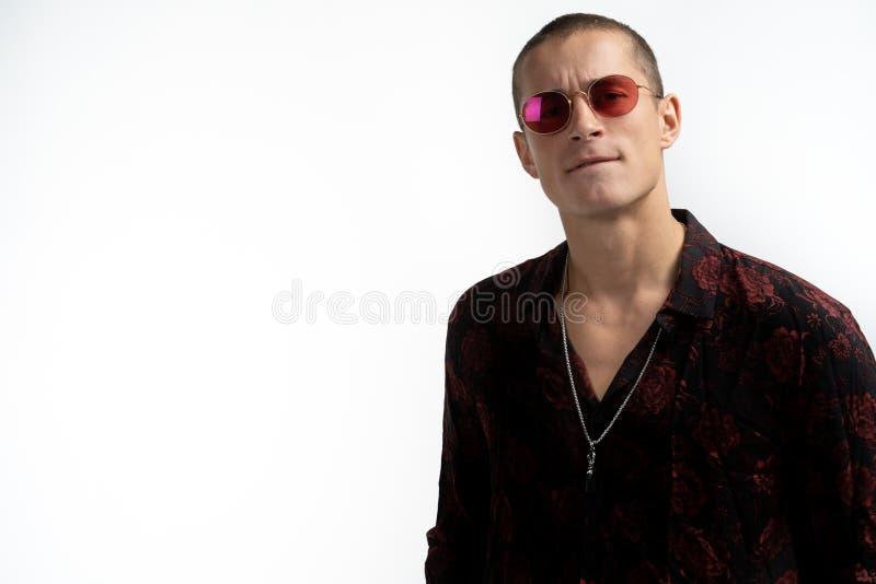 Mezzo ritratto di lunghezza dell'uomo sexy allegro in vetri di sole rossi, camicia nera d'avanguardia d'uso, esaminante la macchi immagini stock