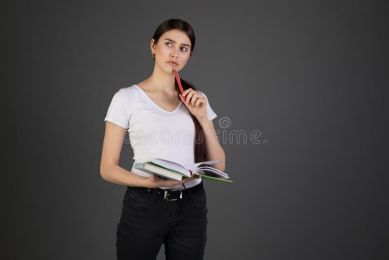 Mezzo ritratto di lunghezza della donna vaga thougtful che tiene penna rossa a disposizione vicino alla bocca, libri in altra man fotografie stock libere da diritti