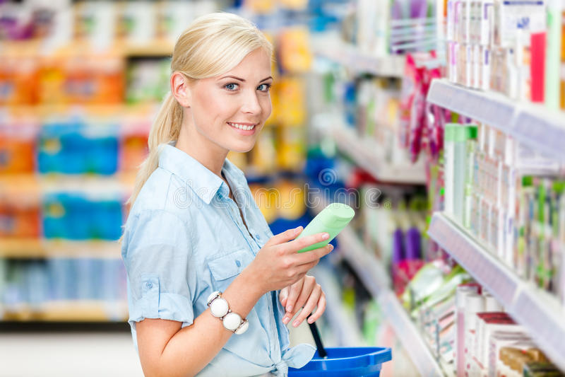 Mezzo ritratto di lunghezza della ragazza al negozio che sceglie i cosmetici fotografie stock