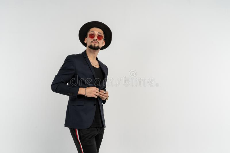 Mezzo ritratto di lunghezza di giovane maschio moderno serio bello che porta vestito e cappello neri in occhiali da sole rotondi fotografia stock