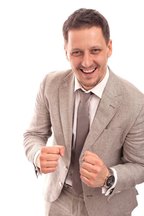 Mezzo ritratto di lunghezza di giovane riuscito uomo d'affari che indossa vestito beige con la mano combattente contro un fondo d fotografie stock