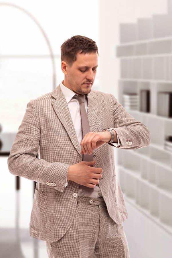 Mezzo ritratto di lunghezza di giovane uomo d'affari serio che indossa vestito beige Sta nell'ufficio ed esamina il suo orologio  immagine stock