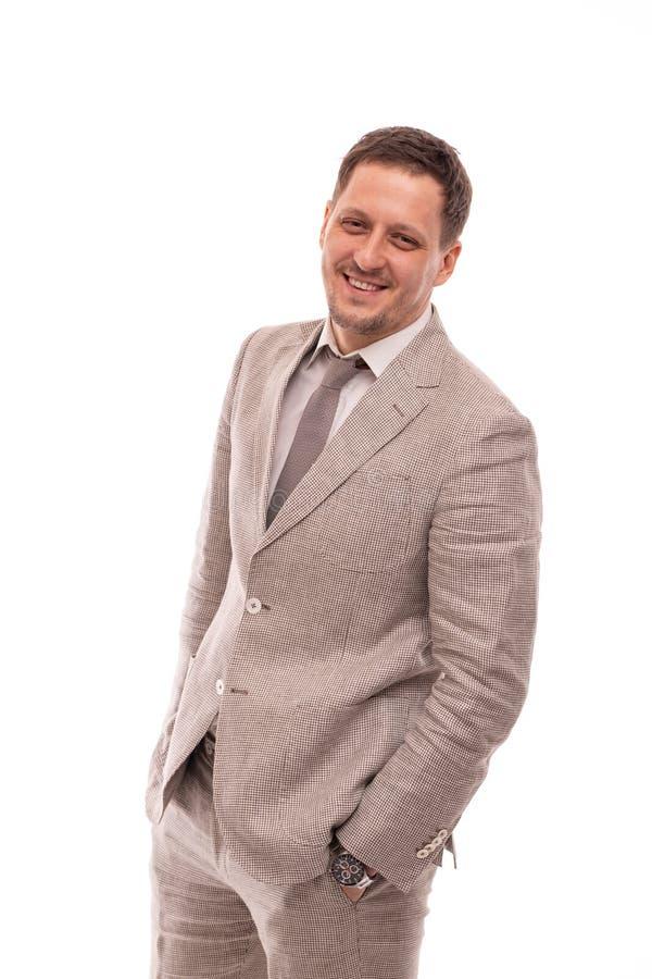 Mezzo ritratto di lunghezza di un giovane che indossa vestito beige, isolato Sta stando con le sue mani in sue tasche e fotografia stock libera da diritti