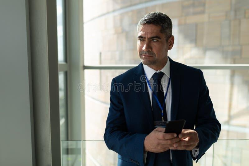 Mezzo sezione di un uomo d'affari che distoglie lo sguardo e che tiene il suo telefono cellulare immagine stock libera da diritti