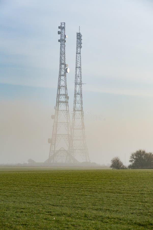 Mgła Zakrywający komunikacja maszty w polu zdjęcia stock