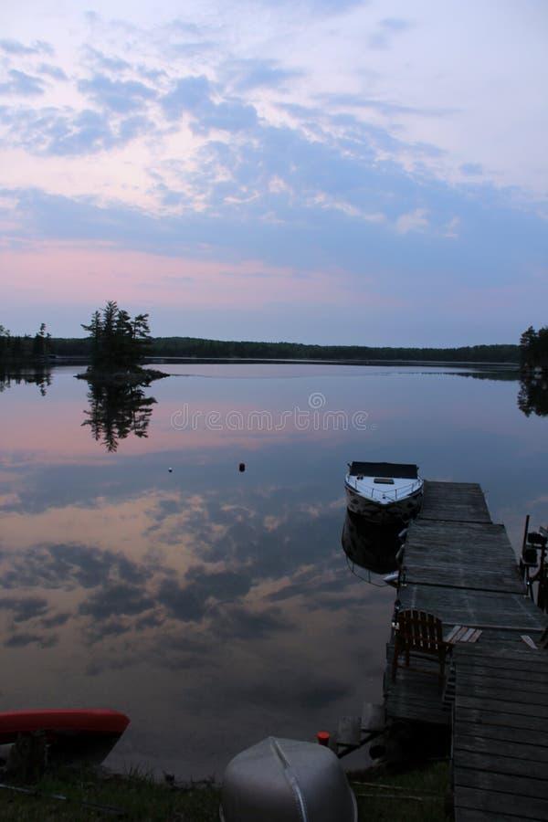 Mgławy wschód słońca nad jeziornego odbicia łódkowatym dokiem fotografia stock