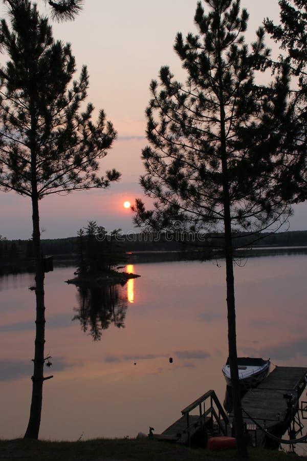 Mgławy wschód słońca nad jeziornym odbiciem zdjęcia royalty free