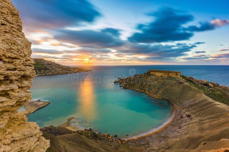 Mgarr,马耳他- Gnejna海湾全景,最美丽的海滩在日落的马耳他与美丽的五颜六色的天空 库存照片
